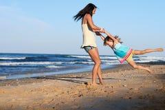 儿童摇摆的父母海滩 免版税库存照片