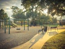 儿童操场活动在日落的住宅区 免版税库存照片