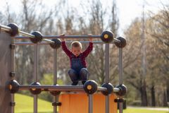 儿童操场爬升套架的愉快的小男孩 免版税库存图片