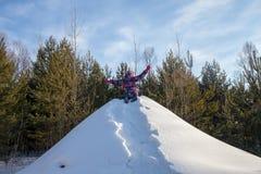 儿童攀登与一支管的小山下降的 孩子在与一张幻灯片的冬天滑雪在管材 对小山和sledding的孩子奔跑 免版税库存图片