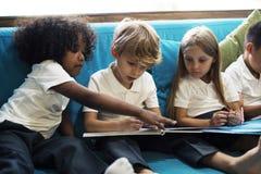 读儿童故事书的年轻学生 免版税库存照片
