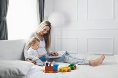 儿童教育 有她的坐床和读书的小孩的愉快的母亲 免版税库存图片
