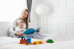 儿童教育 有她的坐床和读书的小孩的愉快的母亲 库存图片
