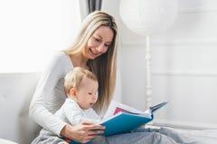 儿童教育 有她的坐床和读书的小孩的愉快的母亲 库存照片