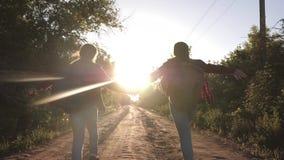 儿童旅客 r 有沿乡下公路跑的背包的愉快的女孩旅客握在光芒的手  股票录像