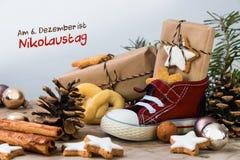 儿童有甜点、礼物和圣诞节装饰品的` s鞋子在ru 图库摄影