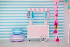 儿童有甜点的` s区域:棒棒糖、冰淇凌、macarons、气球和棒棒糖 有蓝色条纹的儿童居室 免版税库存照片