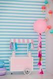 儿童有甜点的` s区域:棒棒糖、冰淇凌、macarons、气球和棒棒糖 有蓝色条纹的儿童居室 免版税图库摄影