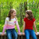 儿童朋友女孩谈话在密林停放森林 免版税库存照片