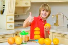 儿童果子女孩愉快的家庭小的桔子 男孩squeez新鲜的橙汁 免版税库存照片