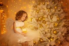 儿童梦想在圣诞树,有蜡烛的愉快的女孩下 免版税库存照片