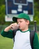 儿童棒球运动员饮用的巧克力牛奶 免版税库存图片