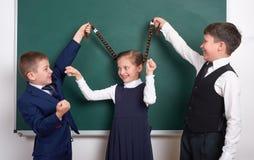 儿童游戏和有乐趣,男孩在空白的学校黑板背景附近拉扯女孩辫子,穿戴在经典黑衣服, grou 库存照片