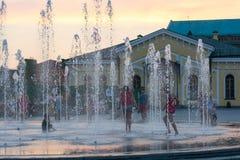 儿童游戏和飞溅在城市` s喷泉在正方形 社论 08 03 2017年 图库摄影