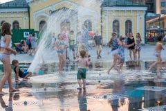 儿童游戏和飞溅在城市` s喷泉在正方形 社论 08 03 2017年 库存图片
