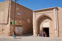 儿童游戏在伊朗沙漠镇历史区域  库存图片