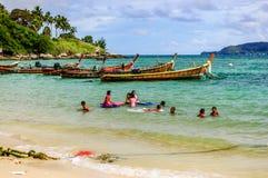 儿童游戏在小船附近的海,普吉岛,泰国 免版税库存图片