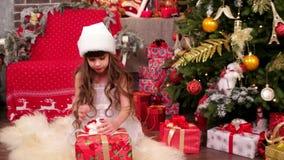儿童游戏在的圣诞前夕,圣诞节惊奇,有看礼物,儿童狂欢节的兴趣的小女孩房子里 股票视频