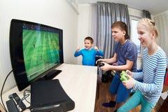 儿童游戏在踢橄榄球的比赛控制台 免版税库存照片
