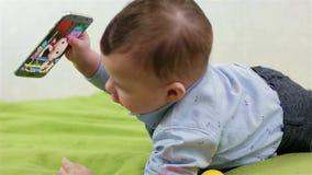 儿童游戏智能手机,爬行在绿色地板,小男孩观看的动画片,孩子上的婴孩获得乐趣 影视素材