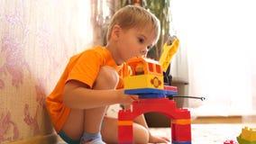 儿童游戏玩具 孩子在使用与建筑集合的游戏室从小立方体收集项目和 股票视频