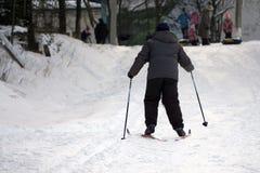 儿童滑雪 与安全帽、风镜和杆的一个活跃孩子 幼儿的滑雪竞赛 家庭的冬季体育 免版税图库摄影