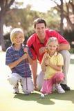 儿童父亲教的高尔夫球作用 免版税库存图片
