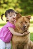 儿童狗拥抱 免版税库存照片