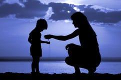 儿童现有量倾吐沙子给妇女 免版税库存图片