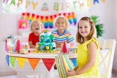 儿童生日宴会 孩子吹在蛋糕的蜡烛 免版税图库摄影