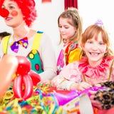 儿童生日聚会的小丑与孩子 免版税库存图片