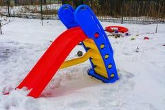 儿童用雪盖的` s玩具在房子的围场 免版税库存照片