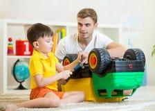 儿童男孩严密地在家使用与卡车玩具 免版税库存图片