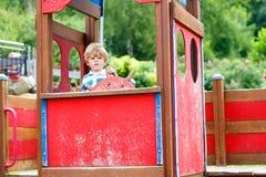 儿童男孩假装驾驶在孩子操场的一辆虚构的汽车 图库摄影