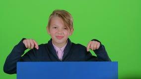 儿童男孩出现从一张蓝色海报的后面看他象再掩藏的展示 绿色屏幕 股票录像