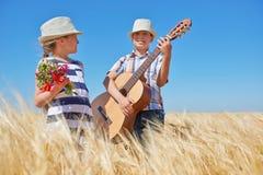 儿童男孩和女孩有吉他的是在黄色麦田,明亮的太阳,夏天风景 免版税库存图片