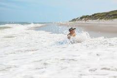 儿童男孩和海波浪飞溅 免版税库存图片