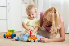 儿童男孩和他的母亲在家修理玩具汽车 图库摄影