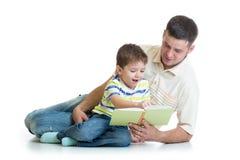 儿童男孩和他的爸爸读了书 免版税库存图片
