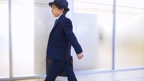 儿童男孩商人在办公室走廊仓促走由工作,侧视图决定 股票录像