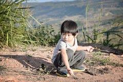 儿童男孩图画到沙子里 免版税库存图片