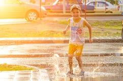 儿童男孩在雨水坑跳  俄国 秋明州 2012年女孩6月哈尔科夫生成少许质量天窗乌克兰的孩子生成 库存照片