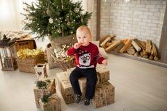 儿童男孩坐礼物盒以圣诞树为背景 免版税库存照片