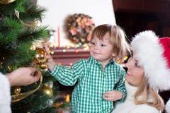 儿童男孩帮助母亲和父亲装饰 免版税图库摄影