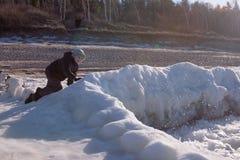 儿童男孩愉快在冬天海岸 免版税图库摄影