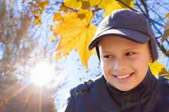 儿童男孩愉快的微笑太阳亮光秋天 免版税库存图片