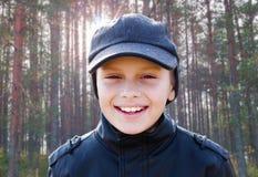 儿童男孩愉快的微笑背后照明画象阳光森林 库存照片