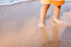 儿童男孩感人的水和身分的脚在海滩 免版税库存照片