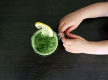儿童男孩递举行健康菠菜绿色菜圆滑的人作为与成份的一份健康夏天饮料在木桌上 Hea 免版税库存图片