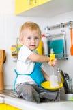 儿童男孩洗涤的盘和有乐趣在 库存图片